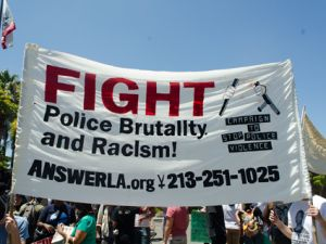 a protest banner that says 'fight police brutality and racism'
